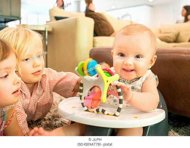 Two young children playing with baby girl