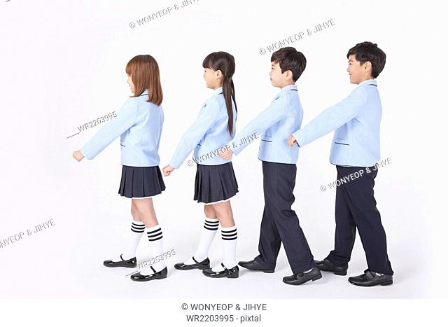 Four elementary school students in school uniforms standing in line and walking together