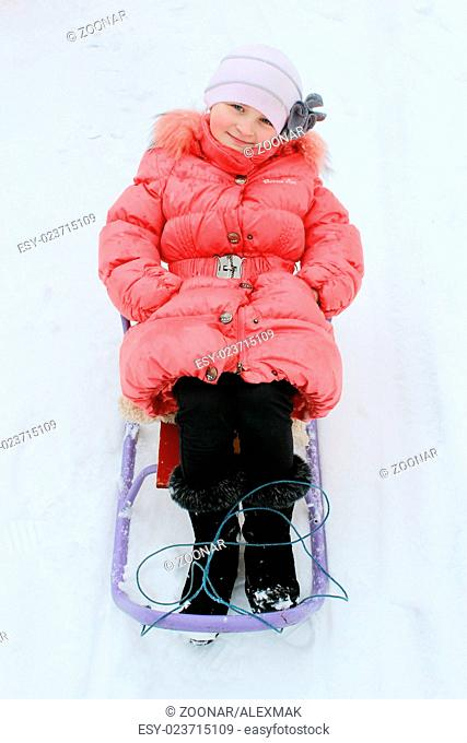 pretty girl sitting on the sledge in the red feath