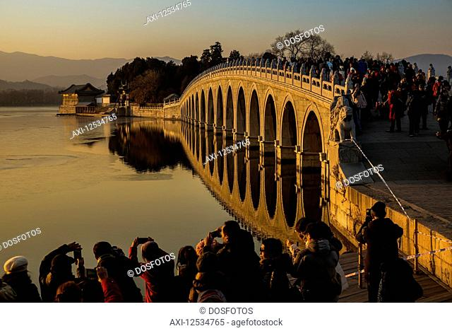 Crowd of tourists taking photographs of the 17 Arch Bridge at sunset, The Summer Palace; Beijing, China