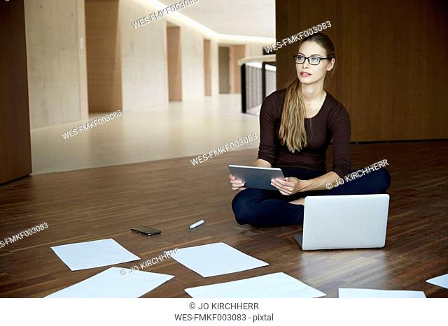 Young woman sitting on floor working with tablet and laptop