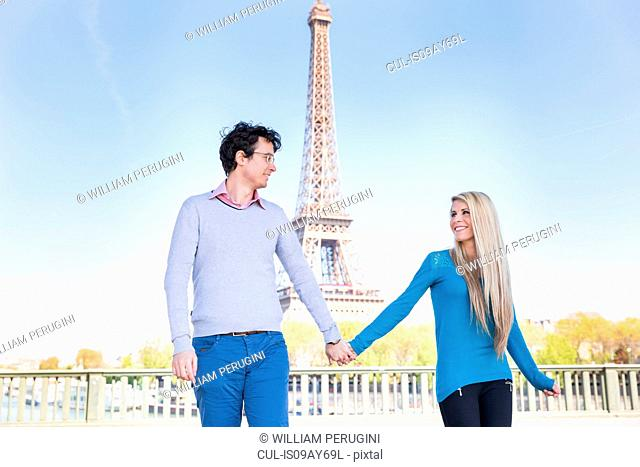 Couple in front of eiffel tower holding hands, Paris, France