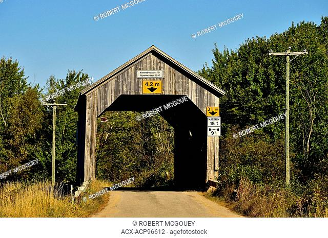 A wooden covered bridge built in 1910, spanning a stream on a two lane road at Plumweseep in rural New Brunswick, Canada