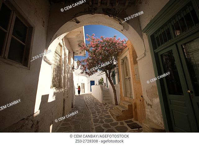 Framed view to the alleys of the town center Parikia with a woman walking in the background, Paros, Cyclades Islands, Greek Islands, Greece, Europe