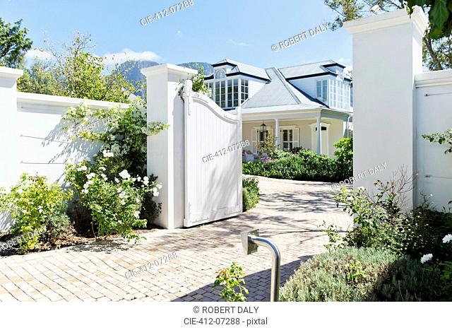 Driveway with open gate to luxury house