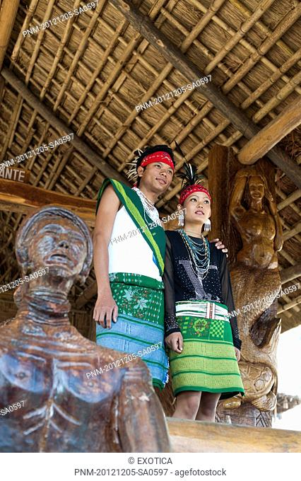 Naga tribal couple in traditional outfit standing in a hut, Hornbill Festival, Kohima, Nagaland, India