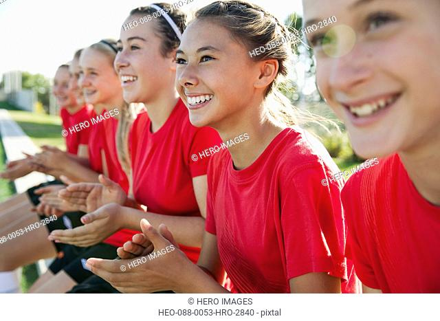 Girl soccer players cheering from bench