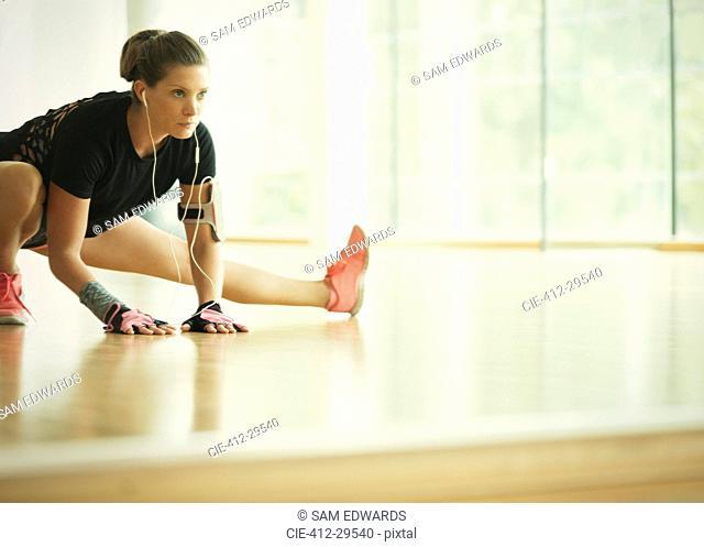 Focused woman stretching leg at gym studio mirror