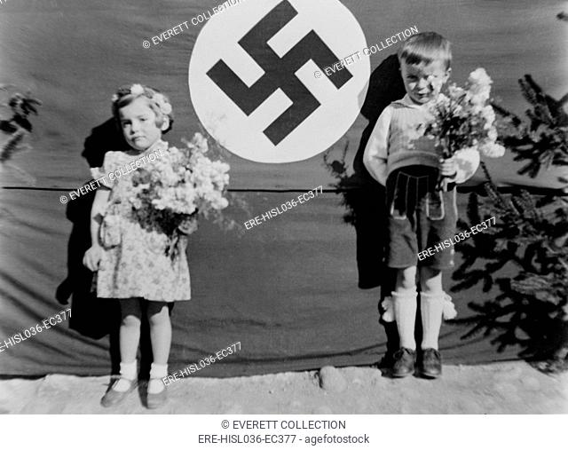 Young German girl and boy at a Nazi ceremony, ca. 1937. They hold flowers and stand beside a large swastika, in Muhldorf am Inn, Germany