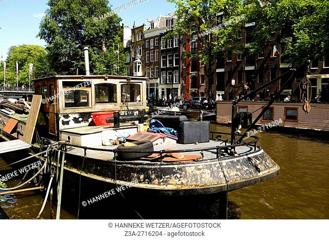 Canal street with houseboat in Amsterdam, the Netherlands, Europe