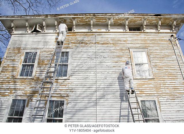 Painters, in protective clothing, scraping paint off an old house