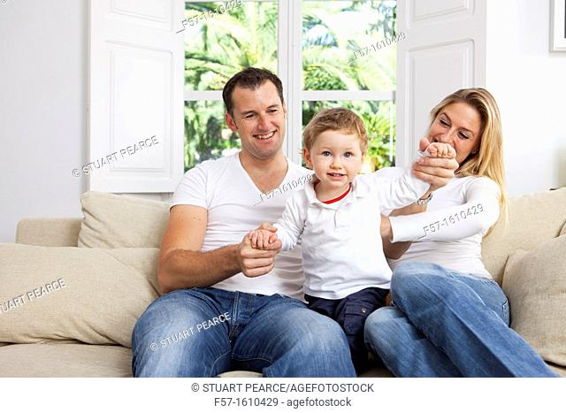 Young family sitting on their sofa at home