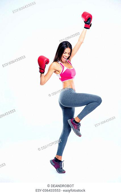 Full length portrait of a fitness woman in boxing gloves celebrating her success over gray background