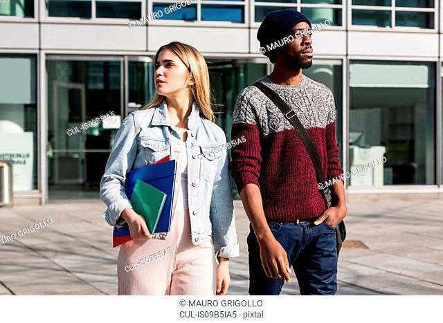 Young man and woman walking outdoors, woman carrying notebooks and files