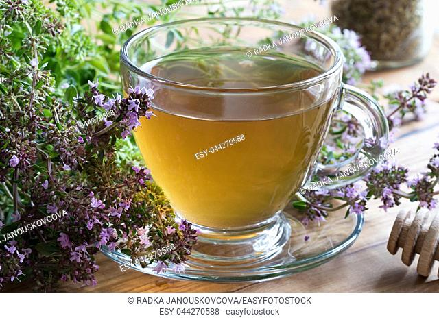 A cup of Breckland thyme (thymus serpyllum) tea, with fresh blooming Breckland thyme on a wooden background