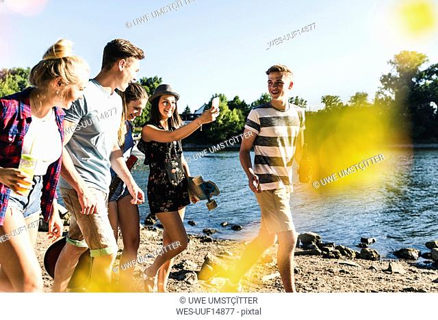Group of happy friends walking at the riverside