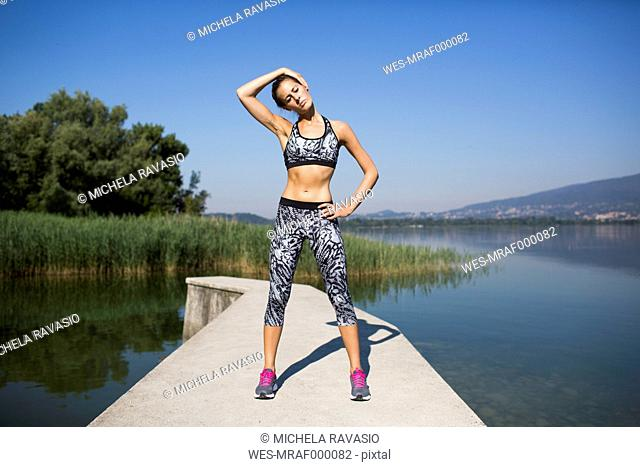Young woman doing exercise at lake