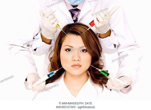 young pretty Asian woman with four needles about to be put into her face