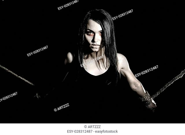 Pale woman with tied arms over black background