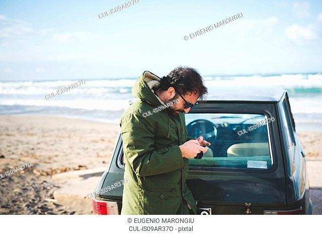 Man with vintage car on beach reading smartphone texts, Sorso, Sassari, Sardinia, Italy