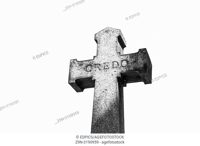 "stone cross bearing the word """"credo"""" against white background, paris, ile de france, france"