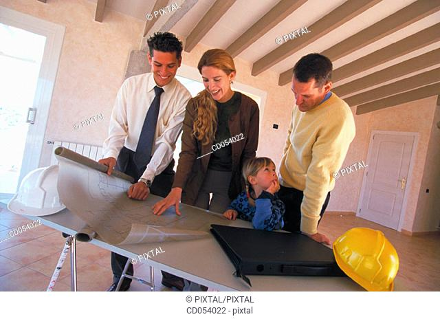 Family looking at blueprint of their new house