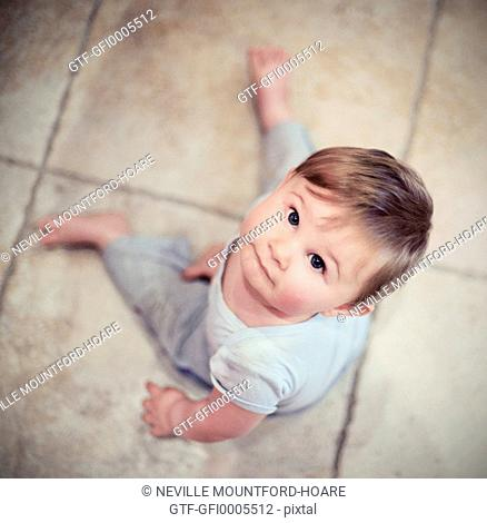 Baby boy sitting on floor looking up