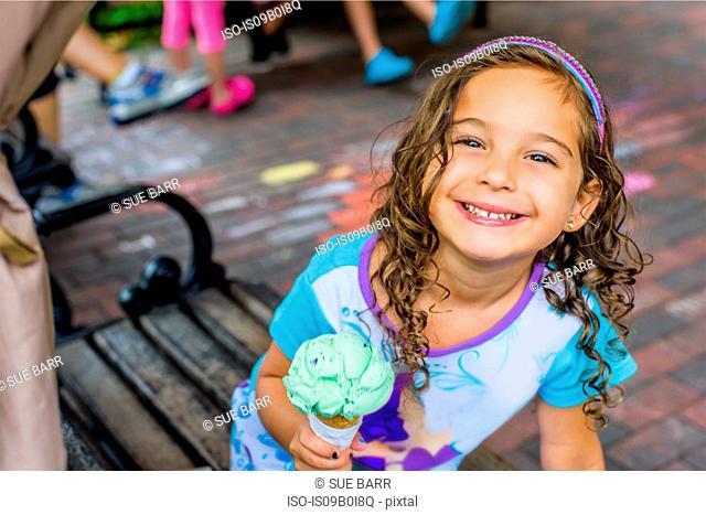 Portrait of cute girl eating ice cream cone on sidewalk