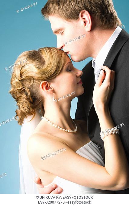 Happy beautiful couple, groom kissing bride forehead