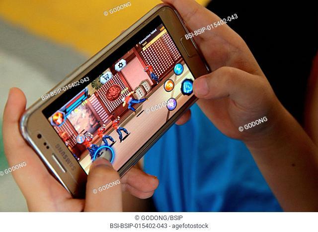 Boy playing on a smartphone. Ho Chi Minh City. Vietnam