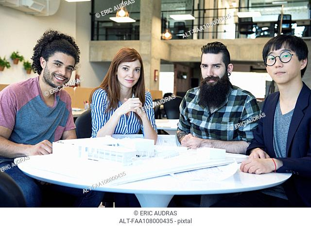Team of architects with building model, portrait