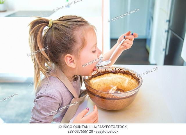 hungry four years old girl tasting or eating chocolate cream with spoon from glass bowl, at kitchen of home