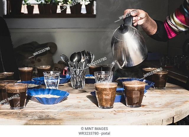 Coffee tasting, barista pouring coffee into glasses on a wooden table, trays with coffee beans