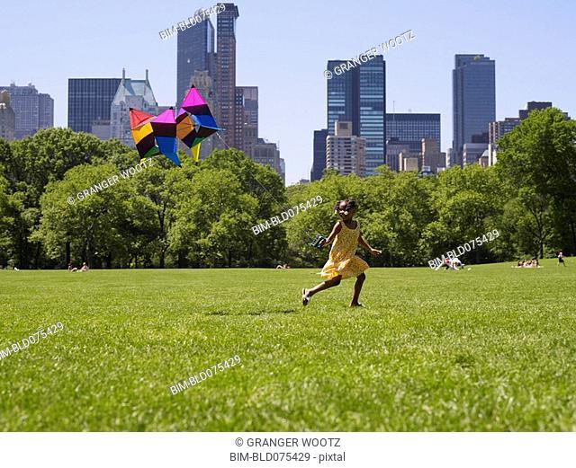 African girl flying kite in park