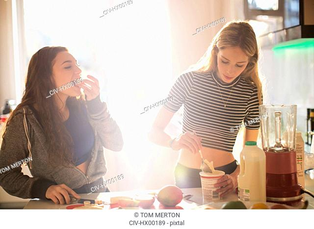 Teenage girls making smoothie in sunny kitchen