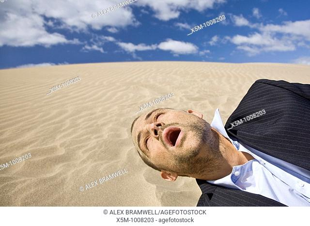 Businessman dying in the desert sun with sand all over his face