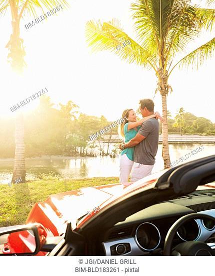 Caucasian couple hugging near convertible