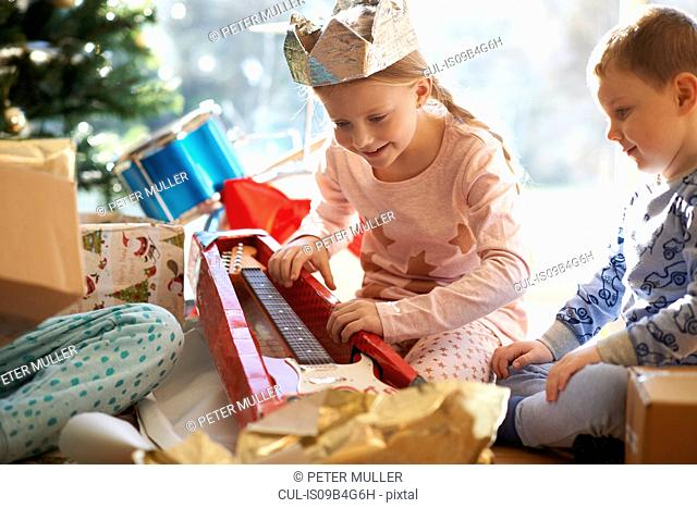 Girl and brother on living room floor gazing at toy guitar christmas gift