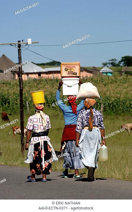 Xhosa women carrying water in buckets and goods in boxes, all on their heads in the Eastern Cape Province of South Africa