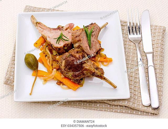 Grilled racks of lamb with onion, garlic and capers, top view
