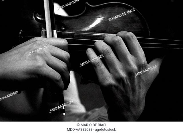 Uto Ughi playing. Detail of the hands of Italian violinist Uto Ughi (Diodato Emilio Ughi) playing the violin. Val Badia, January 1970