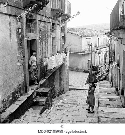 A little girl and a woman standing on the entrance of their house in the neighbourhood called Ragusa Ibla. Ragusa, 1955