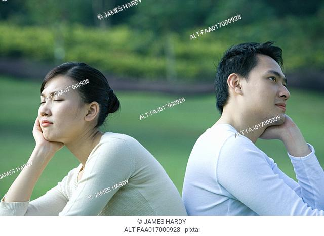 Couple sitting back to back, resting heads in hands