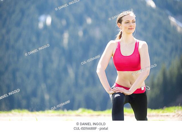 Female jogger stretching on hilltop
