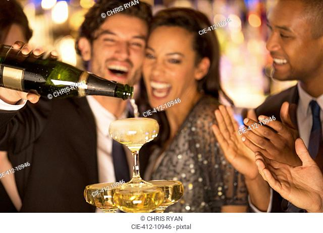 Close up of laughing couple pouring champagne pyramid