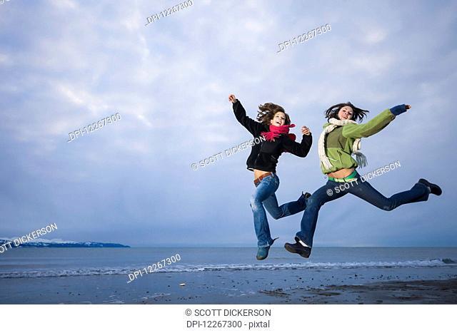 Young women playing and jumping on the Homer Spit, Kenai Peninsula, Southcentral Alaska