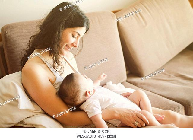 Smiling mother with her baby on sofa