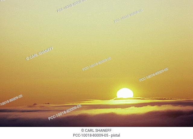 Hawaii, Sunball sinking into clouds in dramatic sunset sky