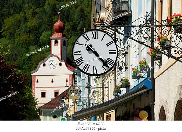 View of a clock hanging from a sign post outside a building, Gmuend, Kaernten, Austria
