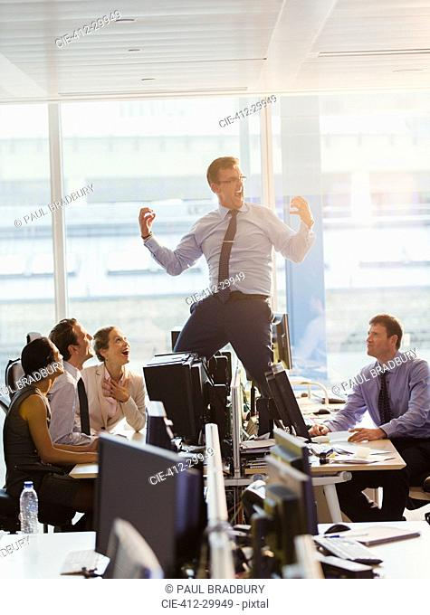 Exuberant businessman celebrating on top of desks in office